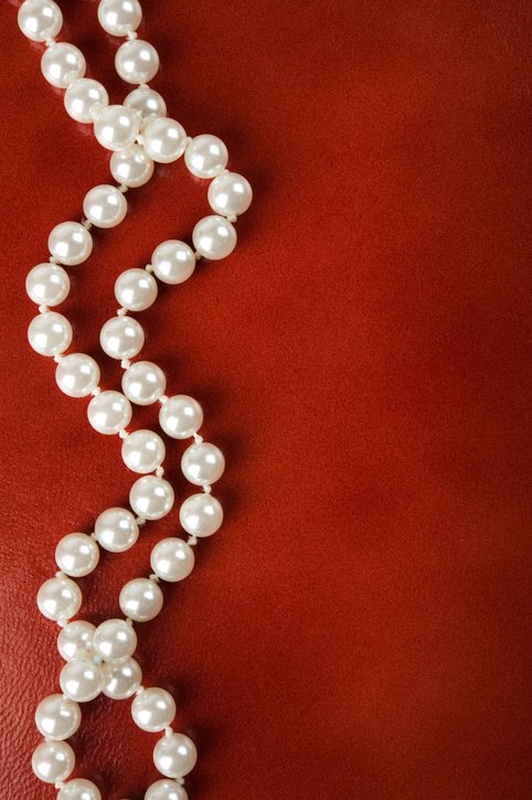 White pearl necklace brown leather background